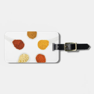 Five seasoning spices on porcelain spoons luggage tag