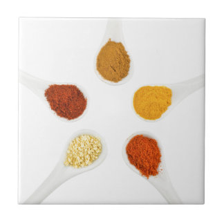 Five seasoning spices on porcelain spoons tile