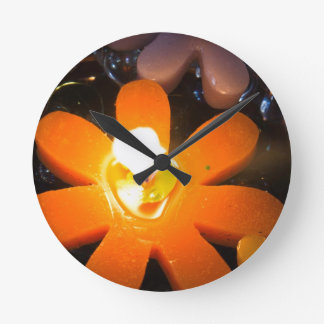 Flame from an orange floating candle wall clocks