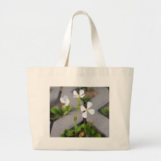 Flower in the parking lot large tote bag