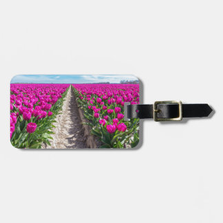 Flowers field with purple tulips and path luggage tag