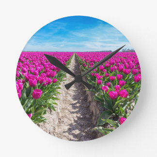 Flowers field with purple tulips and path wall clock