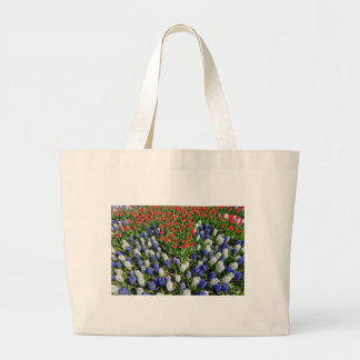 Flowers field with red blue tulips and hyacinths large tote bag