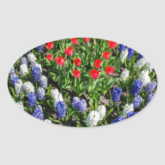Flowers field with red blue tulips and hyacinths oval sticker