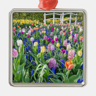 Flowers field with tulips hyacinths and bridge metal ornament