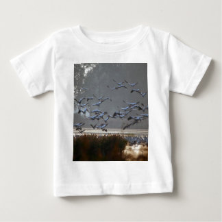 Flying cranes on a lake baby T-Shirt