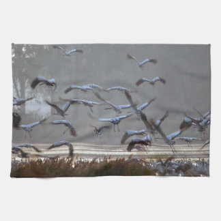 Flying cranes on a lake hand towel