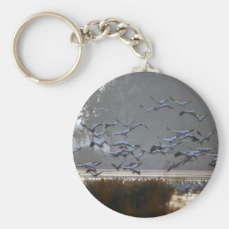 Flying cranes on a lake keychain