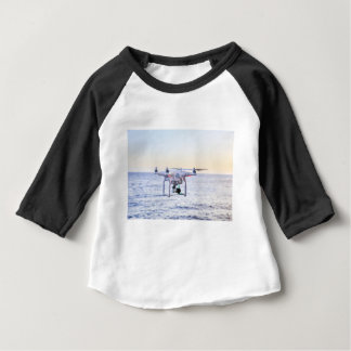 Flying drone at coast above sea baby T-Shirt