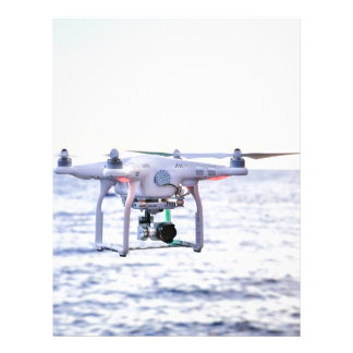 Flying drone at coast above sea letterhead