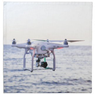 Flying drone at coast above sea napkin