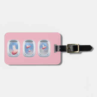 flying pigs seen through an airplane window luggage tag