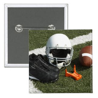 Football, football helmet, tee and shoes on pins