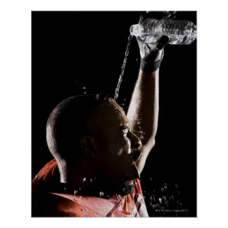 Football player cooling off with water poster