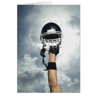 Football player holding helmet in air card