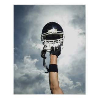 Football player holding helmet in air poster