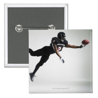 Football player leaping in mid air to catch ball 2 inch square button
