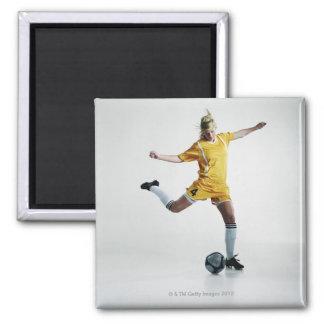 Footballeur féminin disposant à donner un coup de magnet carré