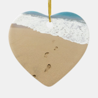 Footsteps in sandy beach leading to blue sea ceramic heart ornament
