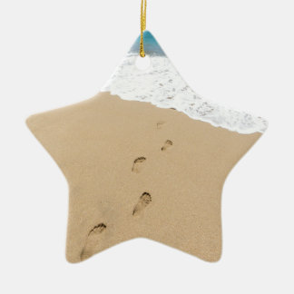 Footsteps in sandy beach leading to blue sea ceramic star ornament