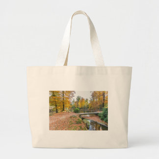 Forest with pond and bridge in fall colours large tote bag