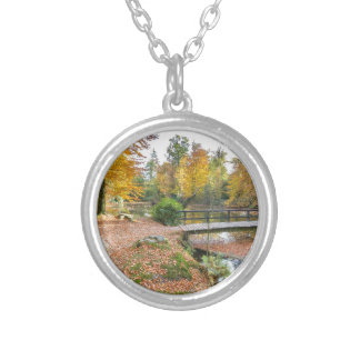 Forest with pond and bridge in fall colours silver plated necklace