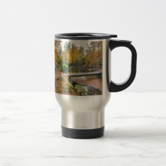 Forest with pond and bridge in fall colours travel mug
