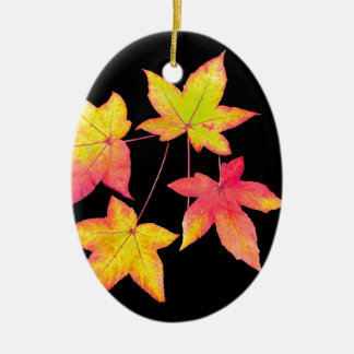 Four colored autumn leaves on black background ceramic oval ornament