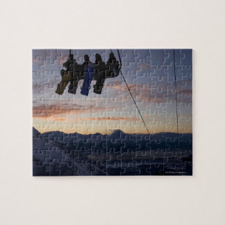 Four snowboarders are silhouetted on a ski lift jigsaw puzzle