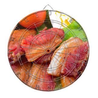Fragment dish closeup with shredded lettuce, tomat dartboard