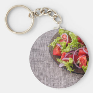 Fragment of a transparent plate with a fresh salad basic round button keychain