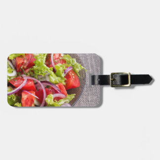 Fragment of a transparent plate with a fresh salad luggage tag