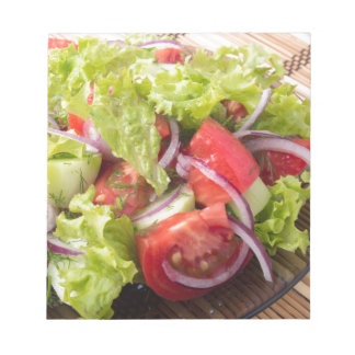 Fragment of vegetarian salad from fresh vegetables notepads
