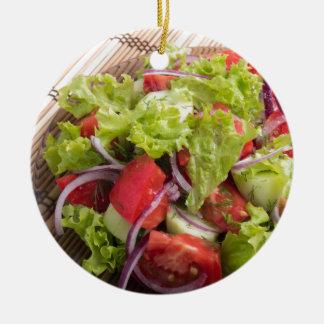 Fragment of vegetarian salad from fresh vegetables round ceramic ornament