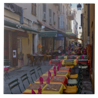 France, Corsica. Tables of cafe set up in narrow Tile
