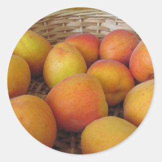 Fresh apricots in a wicker basket classic round sticker