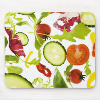 Fresh mixed salad vegetables falling to camera mouse pad