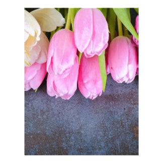 Fresh pink tulips on gray stone background letterhead