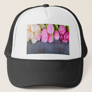 Fresh pink tulips on gray stone background trucker hat