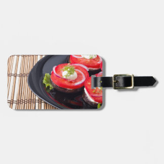 Fresh sliced tomatoes on a black plate close-up luggage tag