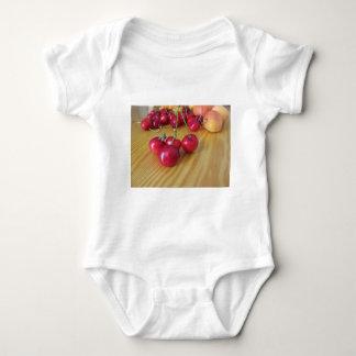 Fresh summer fruits on light wooden table baby bodysuit