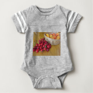 Fresh summer fruits on light wooden table baby bodysuit