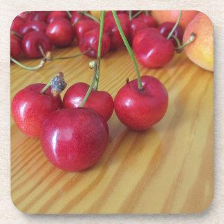 Fresh summer fruits on light wooden table coaster