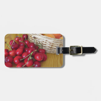 Fresh summer fruits on light wooden table luggage tag