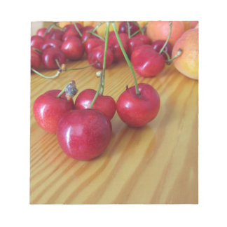 Fresh summer fruits on light wooden table notepad