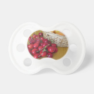 Fresh summer fruits on light wooden table pacifier