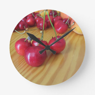 Fresh summer fruits on light wooden table round clock