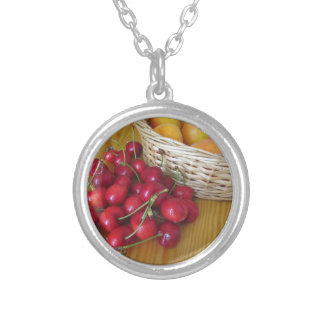 Fresh summer fruits on light wooden table silver plated necklace