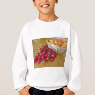 Fresh summer fruits on light wooden table sweatshirt