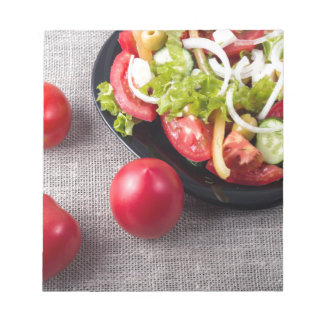 Fresh tomatoes and a part of a plate notepads